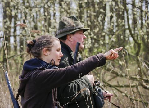 Eine Jägerin und ein Jäger pirschen durchs Revier