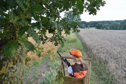 Jägerin auf dem Hochsitz zur Erntejagd