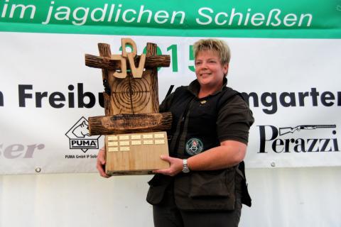 Siegerin mit neu gespendetem Wanderpokal. Die Siegerin schoss das höchste Ergebnis einer Damen bei einer Deutschen Meisterschaft. Der Pokal wurde aus einem Stück Holz mit der Motorsäge geschnitzt.