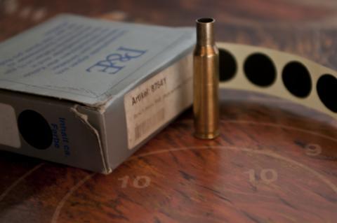 Leere Patronenhülse mit Schießpflastern auf Schießscheibe