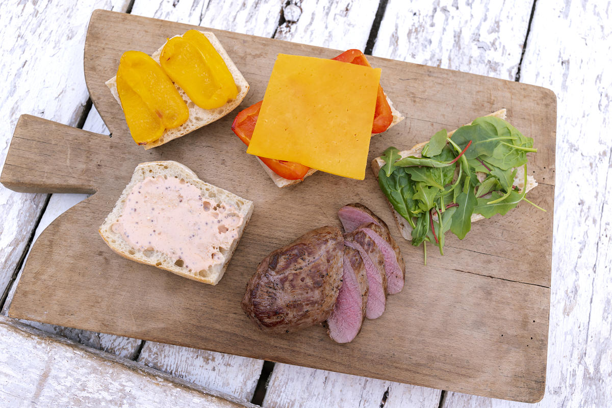 Fleisch in dünne Scheiben schneiden. Die unteren Baguettescheiben mit dem Dressing bestreichen. Darauf den Salat und das Fleisch verteilen. Mit Parmesanhobeln garnieren. (Quelle: Dorn/DJV)