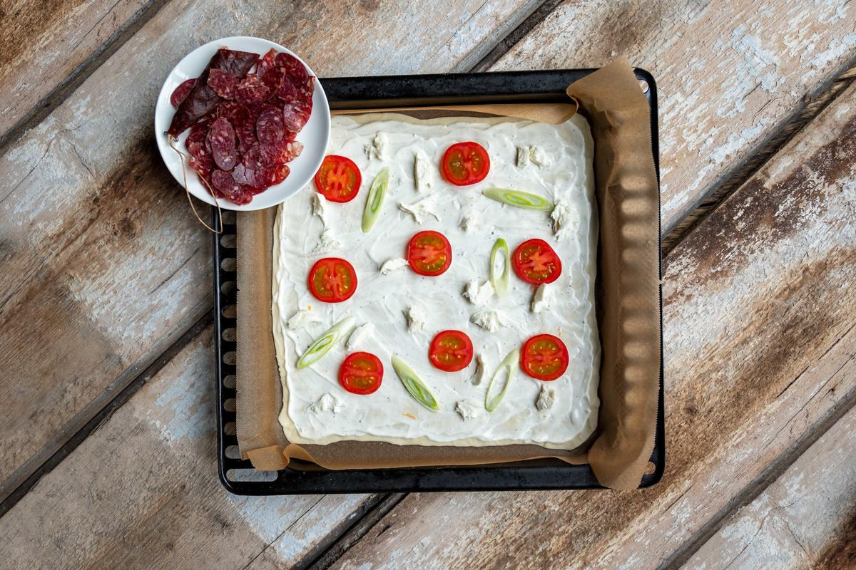 Mit Tomatenscheiben, Frühlingszwiebeln und etwas klein gezupftem Mozzarella belegen. Flammkuchen in den Ofen schieben. Nach ein paar Minuten herausnehmen mit der Wildschweinsalami belegen.  (Quelle: Dorn/DJV)