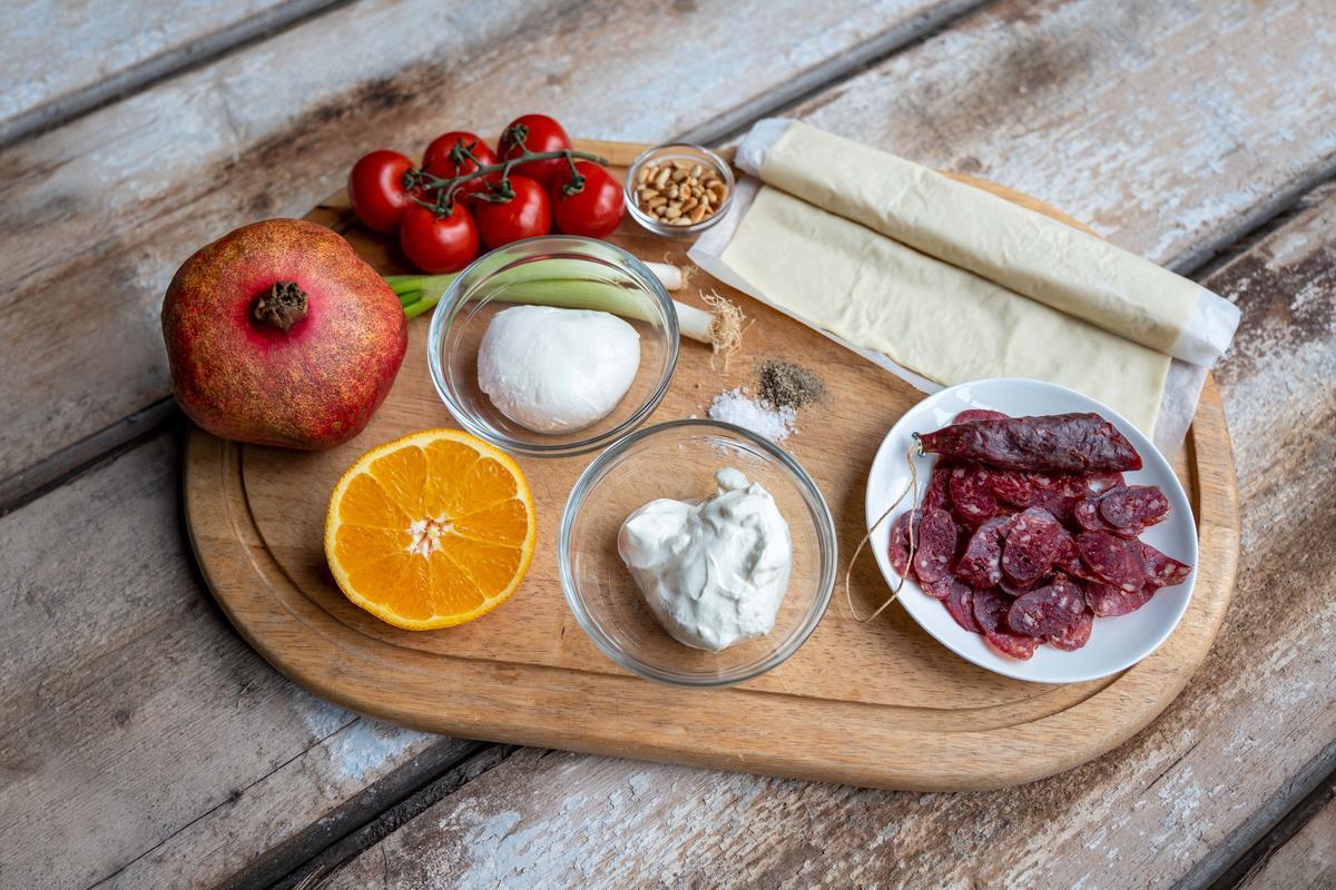 Die Hauptzutaten für das Rezept: Flammkuchenteig, Wildschweinsalami, Tomaten, Schmand, Mozarella, Granatapfel, Orange, Pinienkerne und Lauchzwiebeln.  (Quelle: Dorn/DJV)