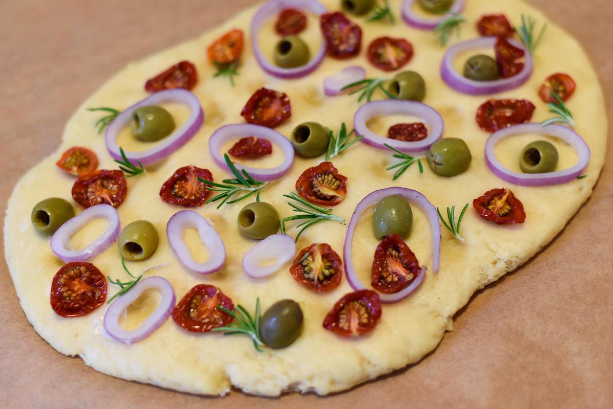 Für das Focaccia Mehl, Salz, Butter, Milch und Hefe mischen. Ruhen lassen und mit Tomaten, Oliven, Zwiebeln und Rosmarin belegen. Im Backofen für 25 bis 30 Minuten backen.  (Quelle: Kapuhs/DJV )