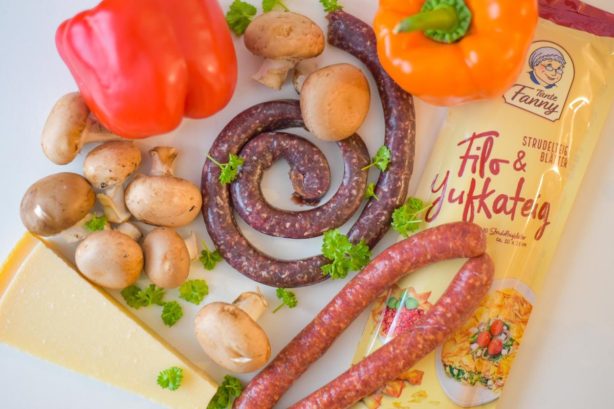 Die Hauptzutaten für das Rezept: Wildwurst, Champignons, Paprika, Filoteig, Parmesan, Petersilie. (Quelle: Kapuhs/DJV)